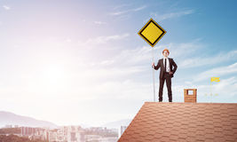 Young businessman on house brick roof holding yellow signboard and looking at city. Mixed media Royalty Free Stock Image