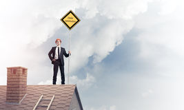 Young businessman on house brick roof holding yellow signboard. Stock Images