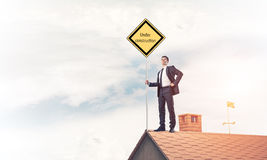 Young businessman on house brick roof holding yellow signboard. Stock Photos