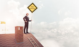 Young businessman on house brick roof holding yellow signboard. Stock Photography