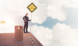 Young businessman on house brick roof holding yellow signboard. Man holding safety sign indicating under construction notice. Mixed media Royalty Free Stock Image