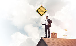 Young businessman on house brick roof holding yellow signboard. Man holding safety sign indicating under construction notice. Mixed media Royalty Free Stock Photos