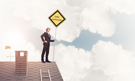 Young businessman on house brick roof holding yellow signboard. Stock Image
