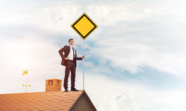 Young businessman on house brick roof holding yellow signboard. Stock Photo
