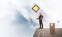 Young businessman on house brick roof holding yellow signboard. Man in suit and helmet holding yellow sign on stick. Mixed media Stock Image