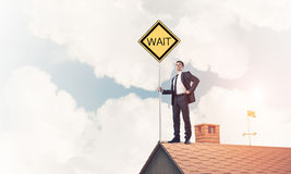 Young businessman on house brick roof holding yellow signboard. Royalty Free Stock Photography