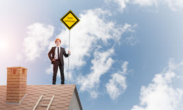 Young businessman on house brick roof holding yellow signboard. Mixed media. Man holding safety sign indicating under construction notice. Mixed media Stock Photography