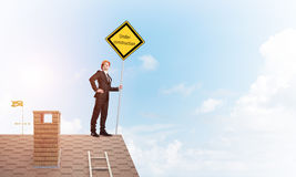 Young businessman on house brick roof holding yellow signboard. Mixed media. Man holding safety sign indicating under construction notice. Mixed media Royalty Free Stock Images