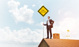 Young businessman on house brick roof holding yellow signboard. Mixed media Royalty Free Stock Photos