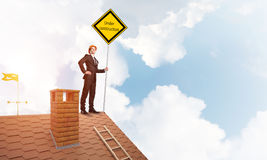 Young businessman on house brick roof holding yellow signboard. Mixed media Royalty Free Stock Photo