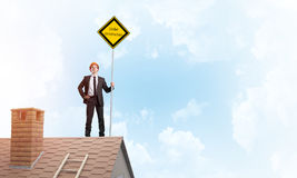 Young businessman on house brick roof holding yellow signboard. Mixed media Royalty Free Stock Image