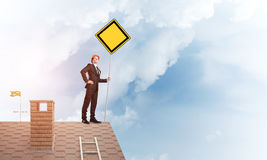 Young businessman on house brick roof holding yellow signboard. Mixed media Royalty Free Stock Photography