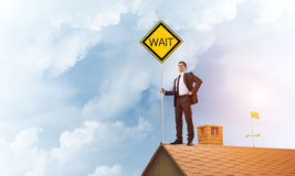 Young businessman on house brick roof holding yellow signboard. Mixed media Stock Image