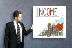 Young businessman with income sketch. Handsome young businessman on concrete background with income sketch on poster Stock Image