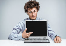 Young businessman indicates a screen laptop. Royalty Free Stock Photography