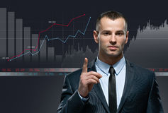 Young businessman with infochart on black background Royalty Free Stock Photos