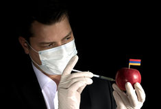 Young businessman injecting chemicals into an apple with Armenian flag Stock Photo