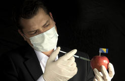 Young businessman injecting chemicals into an apple with Bosnia Stock Images