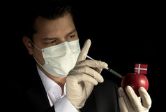 Young businessman injecting chemicals into an apple with Danish royalty free stock images