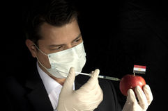 Young businessman injecting chemicals into an apple with Egyptian flag on black background stock photos