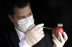 Young businessman injecting chemicals into an apple with Iranian flag. On black background Stock Photo