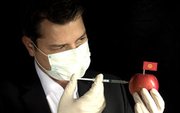 Young businessman injecting chemicals into an apple with Kyrgyzstan flag on black background Royalty Free Stock Image