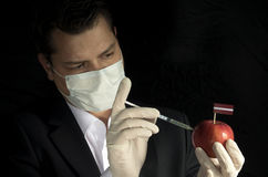 Young businessman injecting chemicals into an apple with Latvian flag on black background royalty free stock photography