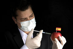 Young businessman injecting chemicals into an apple with Spanish. Flag on black background Royalty Free Stock Photos
