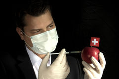 Young businessman injecting chemicals into an apple with Swiss f royalty free stock photography