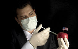 Young businessman injecting chemicals into an apple with United. States flag on black background Stock Images