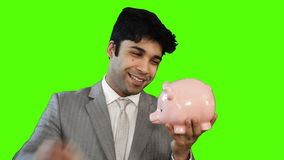Young businessman inserting money into a piggy bank on green background stock footage