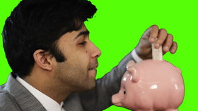 Young businessman inserting money into a piggy bank on green background stock video footage