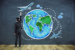 Businessman with tourism sketch. Young businessman in interior with creative globe and tourism sketch stock photography