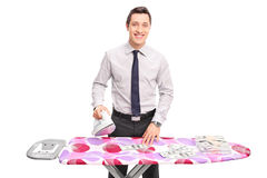 Young businessman ironing money Royalty Free Stock Images