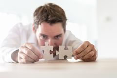 Young businessman joining two matching puzzle pieces royalty free stock image