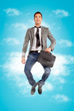 Young businessman jumping with briefcase Stock Photography
