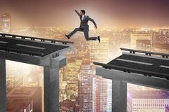 The young businessman jumping over the bridge. Young businessman jumping over the bridge Royalty Free Stock Images