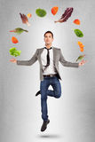 Young businessman jumping with vegetables in the air Royalty Free Stock Photos