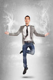 Young businessman jumping on yoga position with smoke. Stock Photos