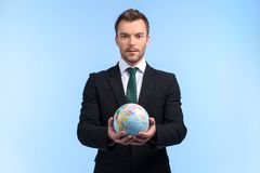 Young businessman keeps world in his hands. Stock Images