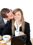 Young businessman kissing his delighted girlfriend Royalty Free Stock Images