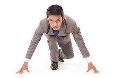 Young businessman kneeling as if about to start a race Royalty Free Stock Photo