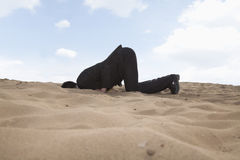 Young businessman kneeling with his head in a hole in the sand Stock Photography