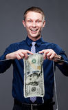 Young businessman is knitting a dollar banknote. Royalty Free Stock Photos