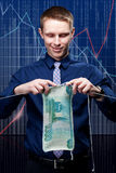 Young businessman is knitting a ruble banknote. Royalty Free Stock Photography