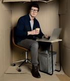 Young businessman is laboring in confined cardboard room. Feeling uncomfortable concept. Full length portrait of manager is sitting at table in cramped carton royalty free stock photo