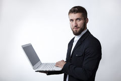 Young businessman with a laptob. Attractive businessman with a Laptop and looking at camera Stock Photo