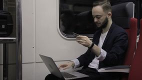 Young businessman with laptop and credit card is sitting in train. Confident professional enters data, working with device during business trip. Bearded guy is stock footage