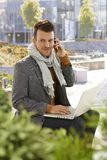 Young businessman with laptop and mobile outdoors Royalty Free Stock Photography