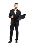 Young businessman with laptop showing thumbs up o.k. hand sign gesture Royalty Free Stock Photos
